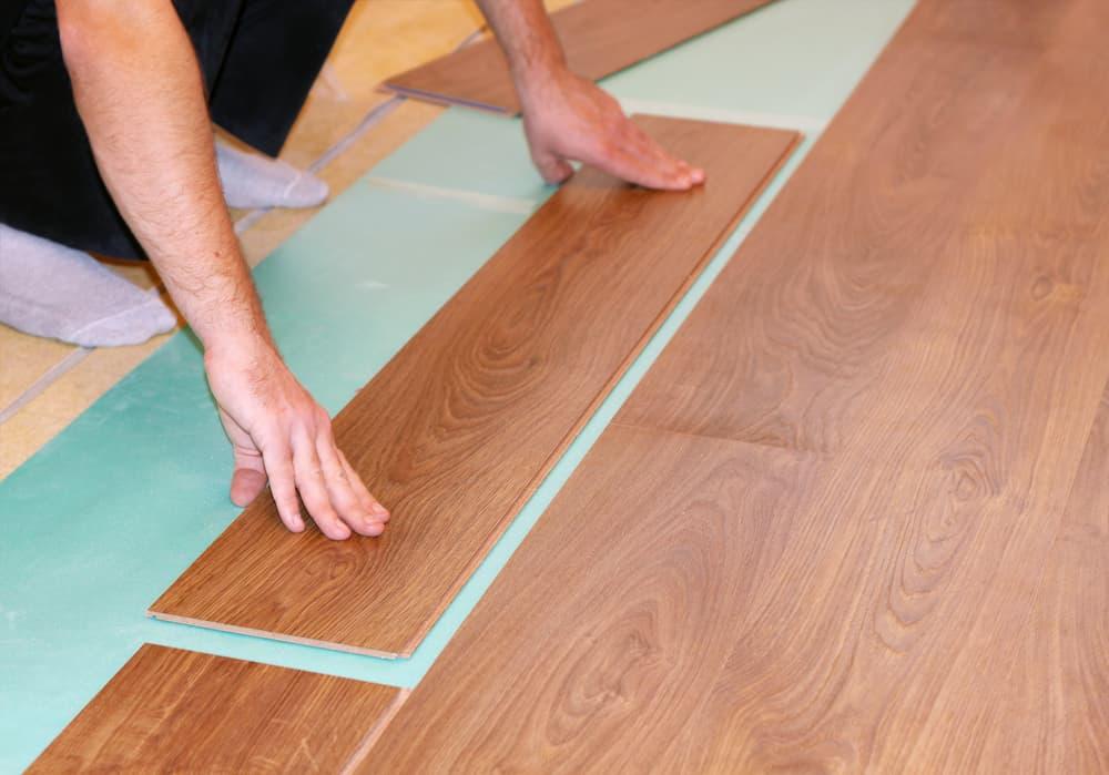 worker installs laminate flooring